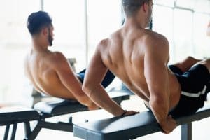 Strong men are doing abs crunches on bench in gym