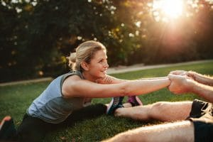 Young health couple exercising in park. Man holding hands of woman and stretching.