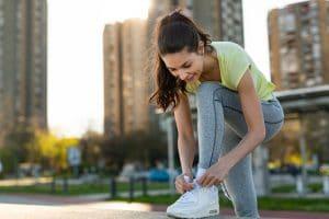 Young sporty beautiful woman tying sports shoe
